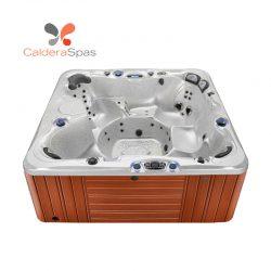 A Caldera Niagara hot tub with a White Sands shell and Redwood siding.